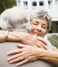 Senior couple hugging outside their home